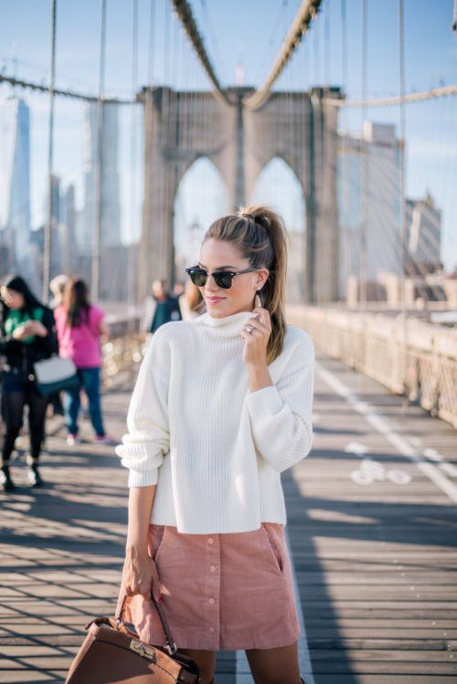 a white turtleneck slouchy sweater, a pink pocket mini skirt with a row of buttons and a brown bag