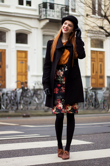 With orange shirt, floral skirt, flat boots and gloves