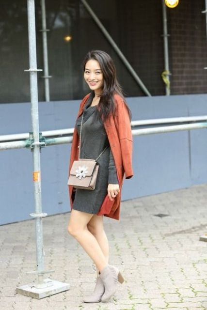 a grey sweater dress, a burnt orange coat, grey suede booties and a matching bag