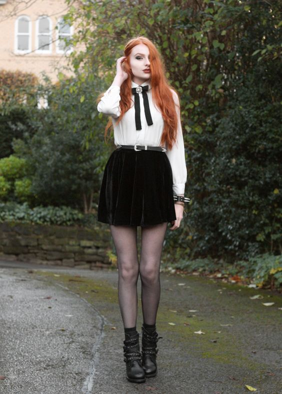 a white vintage-style shirt with a black bow and a brooch, a black velvet mini skirt, black tights and boots