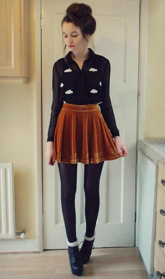 a mustard velvet mini skirt, a black sheer blouse over a top, black tights and booties