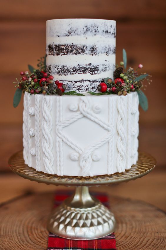 a wedding cake with a cable knit layer and a naked top, with pinecones, berries and foliage