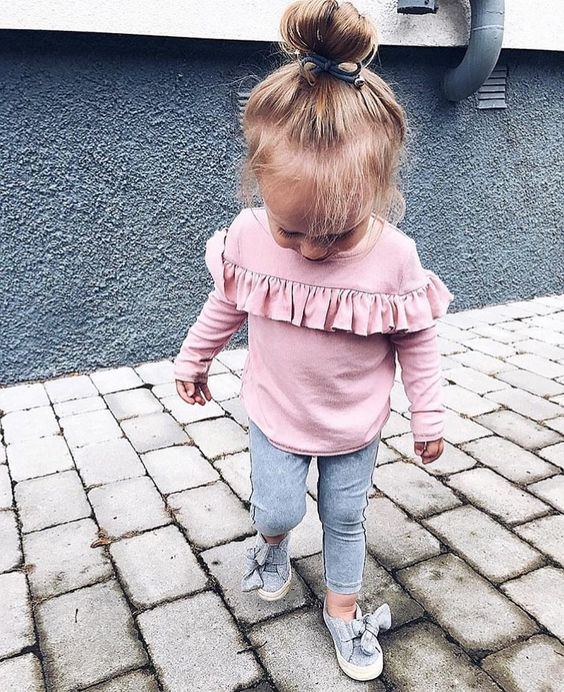 a pink shirt with ruffles, grey leggings and grey flats with bows