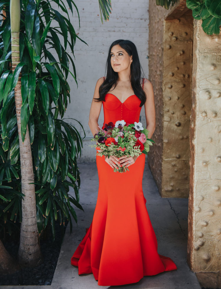 The bride was wearing a fiery red wedding dress with a mermaid silhouette, a train, a sweetheart neckline and a button row on the bodice