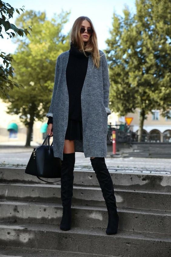 a black pleated mini, a black turtleneck sweater, black tall boots and a grey coat