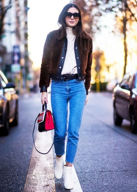 With white turtleneck, crop jeans, white ankle boots and black and red bag