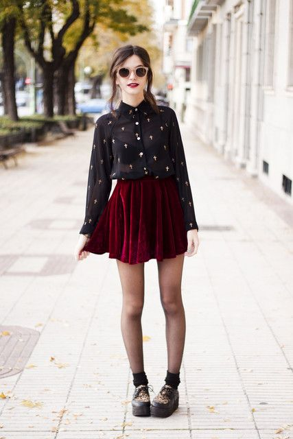 a red velvet mini pleated skirt, a black sheer shirt with a print, black tights and black boots