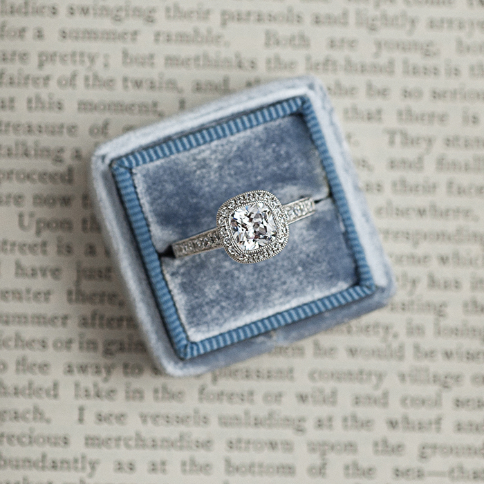 Cushioned halo engagement ring with velvet ring box
