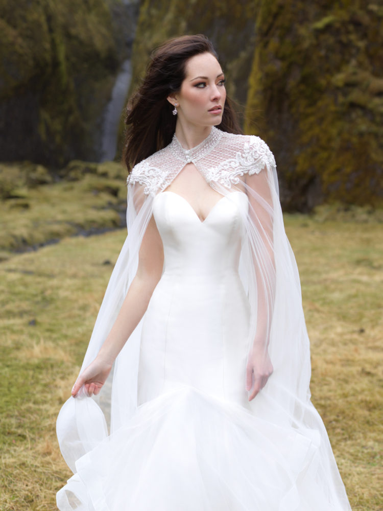 An elegant strapless wedding dress with a ruffled tail and a gorgeous lace beaded cape to highlight it