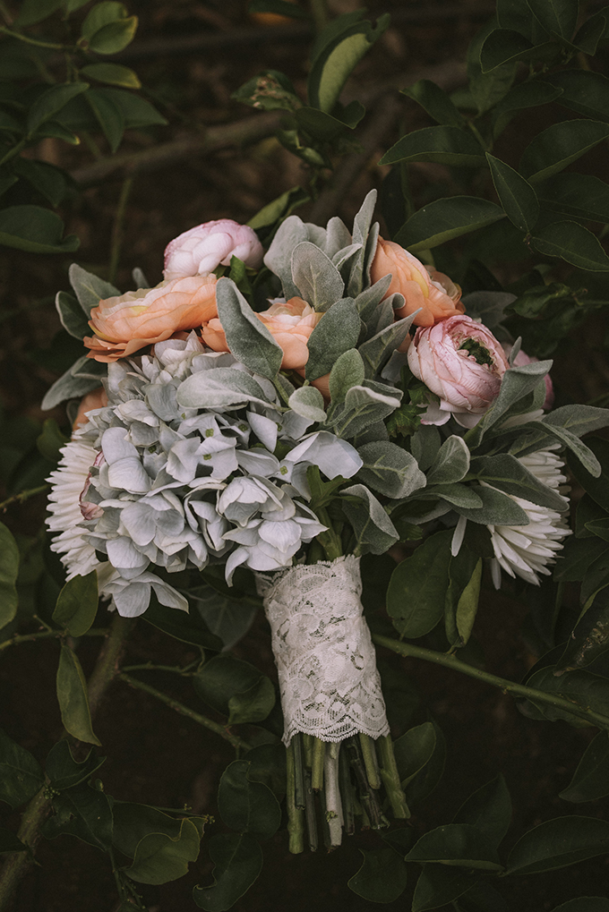 The wedding bouquet was done in pastel pink and orange, with pale greenery and a lace wrap