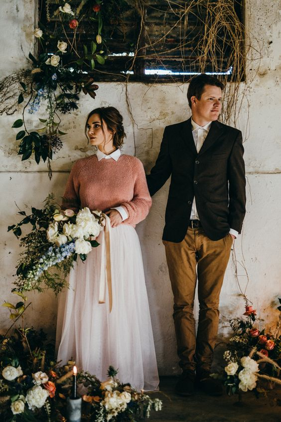 a bride rocking a pink sweater over her wedding dress to make a colorful statement