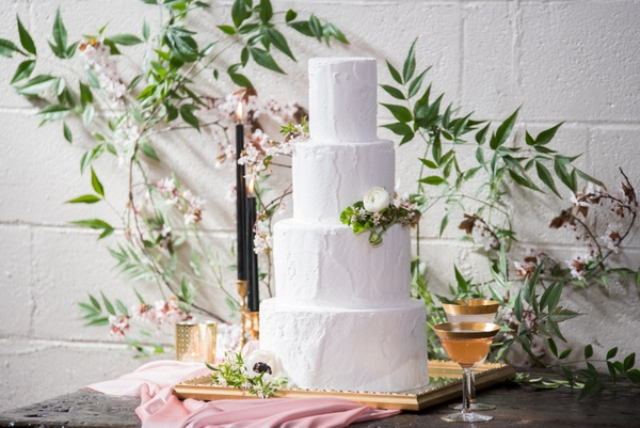 The wedding cake was a white frosted one with greenery, blooms served on a vintage mirror, with black ccandles and flowers in the backdrop