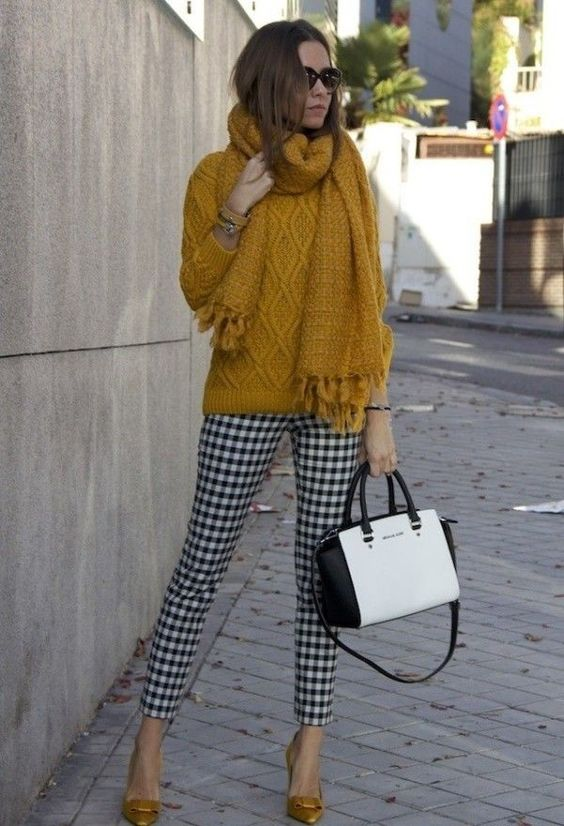 a mustard sweater and scarf, checked black and white pants and mustard shoes