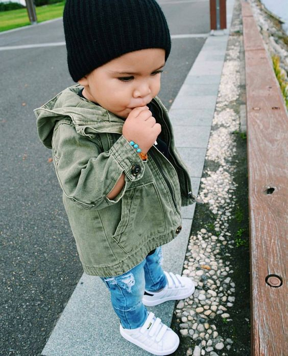 distressed blue jeans, white sneakers, an olive green denim jacket and a black beanie