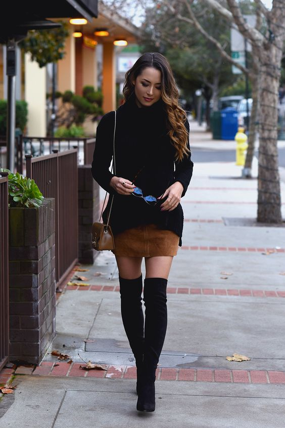 a black sweater, an ocher suede mini skirt, black suede tall boots and a small bag