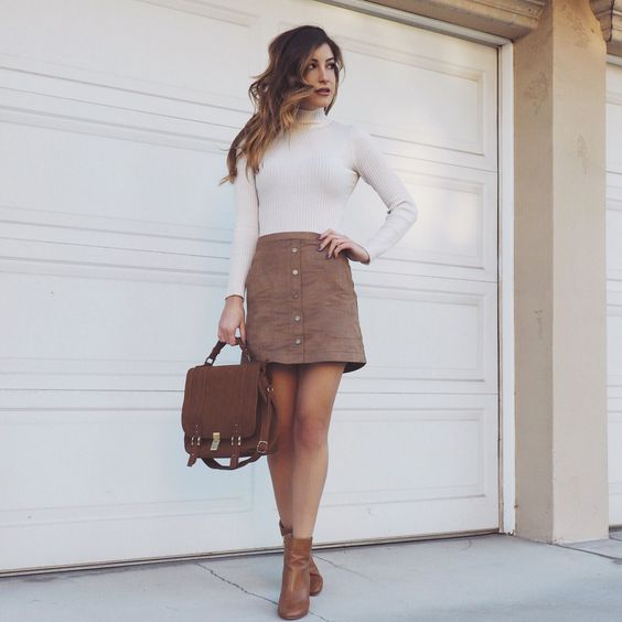 a white turtleneck, a brown mini skirt with a row of buttons, brown booties and a backpack