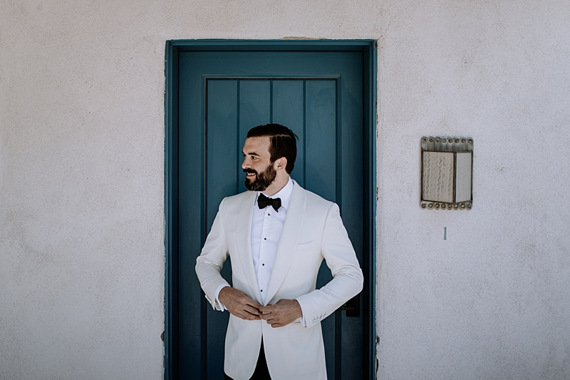 groom looks in white tuxedos - http://ruffledblog.com/laid-back-los-poblanos-wedding-with-orange-bridesmaid-gowns