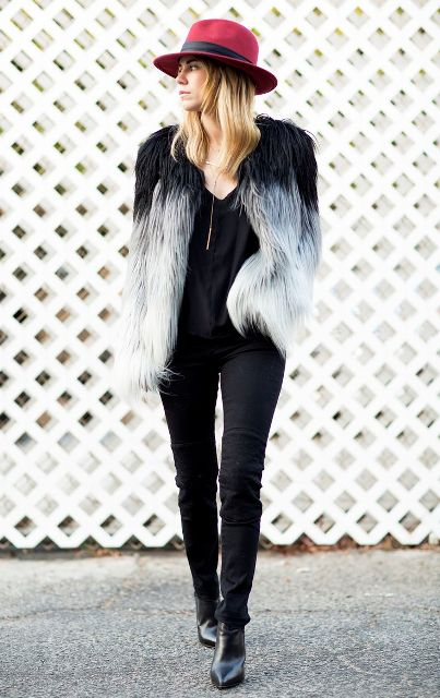 With black blouse, skinny pants, heeled boots and red hat