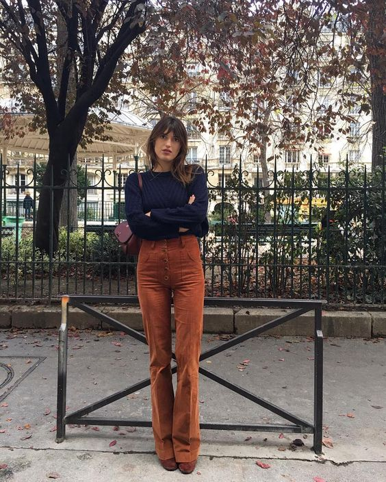 vintage-inspired high waisted burnt orange pants, a navy sweater, matching orange shoes and a purple bag
