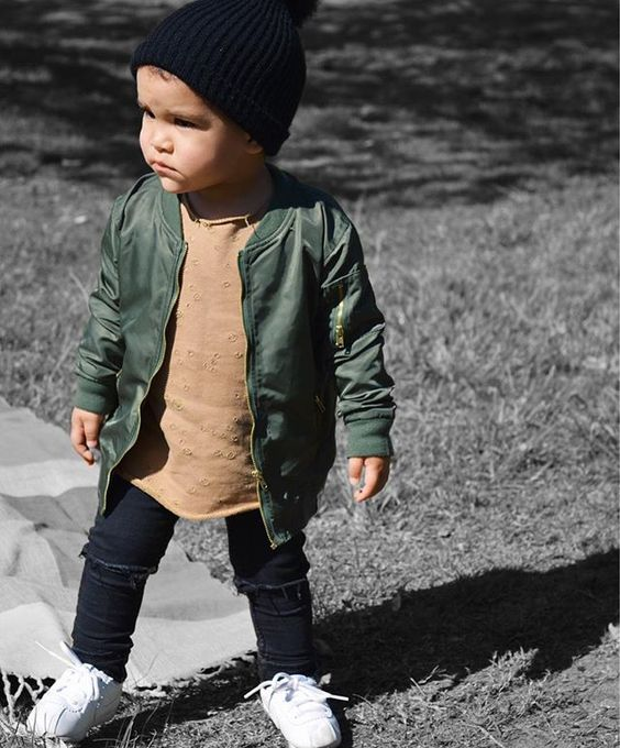 black ripped jeans, a tan shirt, an olive green jacket, white sneakers and a black beanie