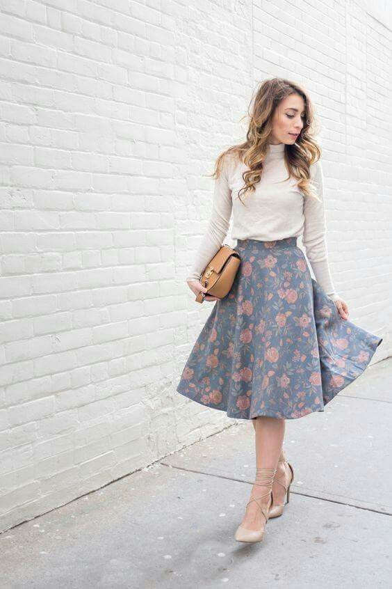 a neutral turtleneck, a pale blue floral print midi skirt, neutral lace up shoes
