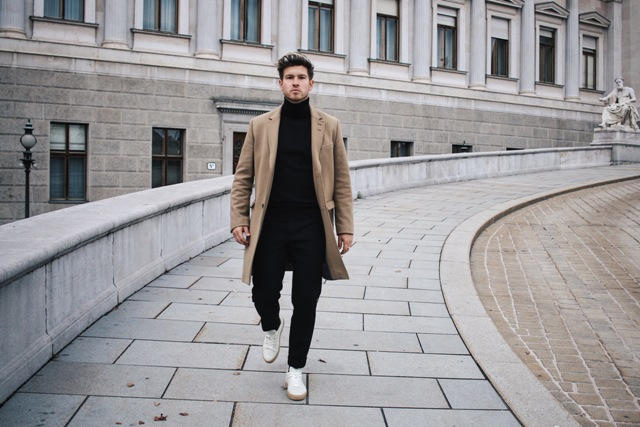 With camel coat, black pants and white shoes
