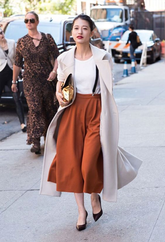 a white tee, burnt orange culottes, brown shoes, black suspenders and a creamy coat