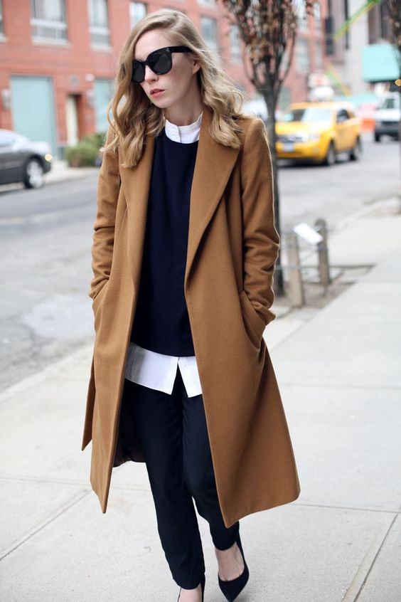 black pants, a black sweater over a white shirt, black suede shoes and a camel coat