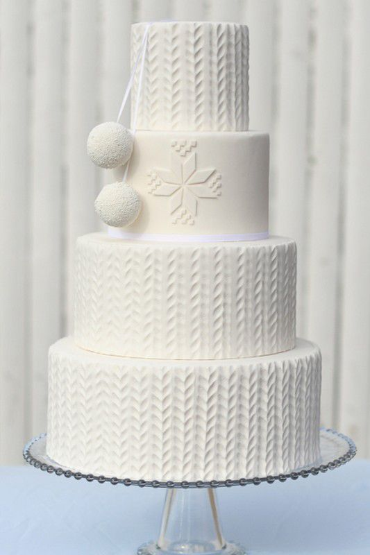 a gorgeous knit cake with edible pompoms and traditional knit patterns