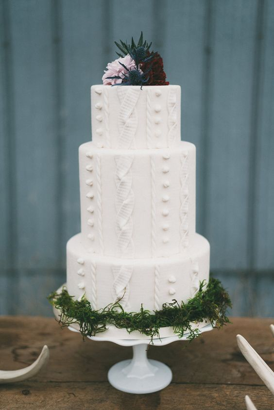 a cable knit wedding cake with moss and topped with thistles, a lavender rose and a burgundy one