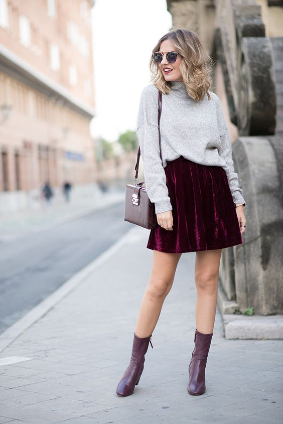 a grey turtleneck, a plum-colored velvet mini skirt, plum sock booties