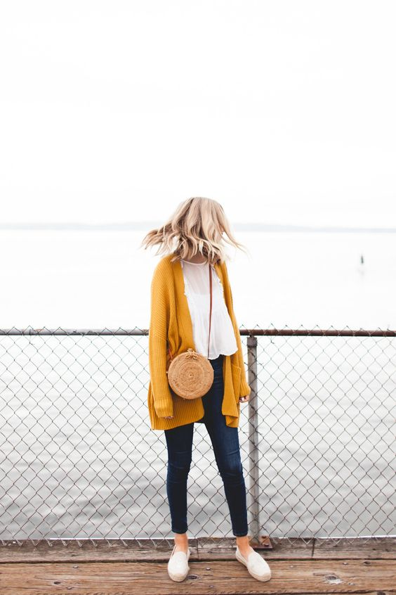 navy jeans, a white top, a mustard cardigan and white moccasins for a weekend look