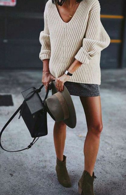 a neutral low cut sweater, a grey mini skirt, green suede boots and a black bag