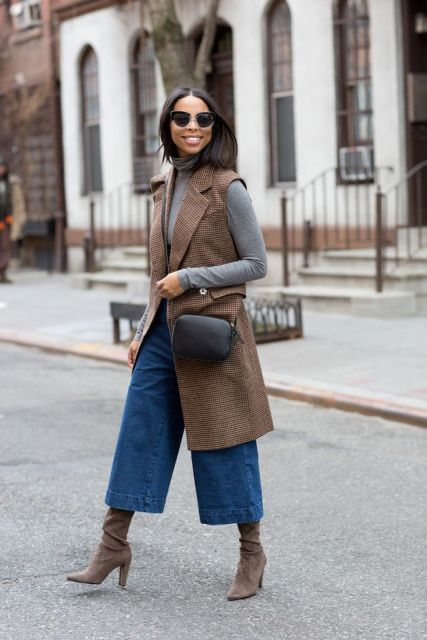 With gray turtleneck, brown long vest, boots and black bag