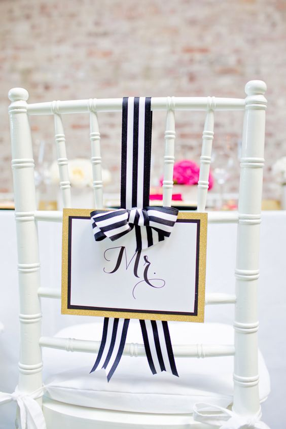 a glam wedding sign with gold glitter, framing and black and white striped bow for a cute wedding