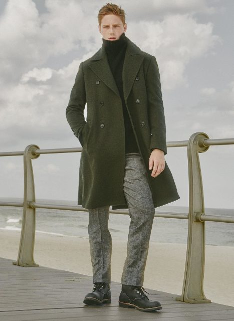 With olive green coat, gray pants and boots