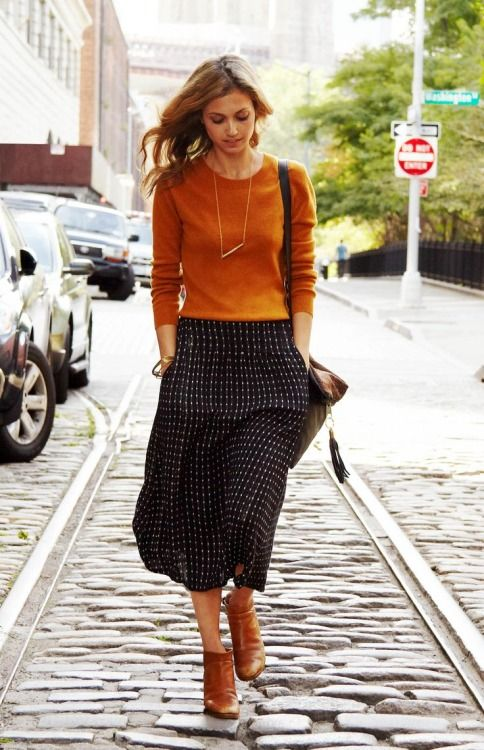a burnt orange long sleeve top, a printed midi skirt, cognac booties for a chic look