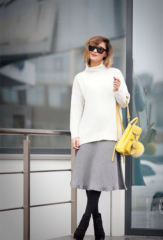 a grey midi skirt, a white turtleneck sweater, black tights, black booties and a yellow backpack