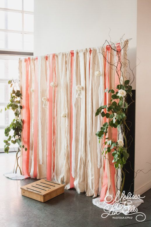 a pink and cream ribbon backdrop with some fresh greenery and white blooms on the sides