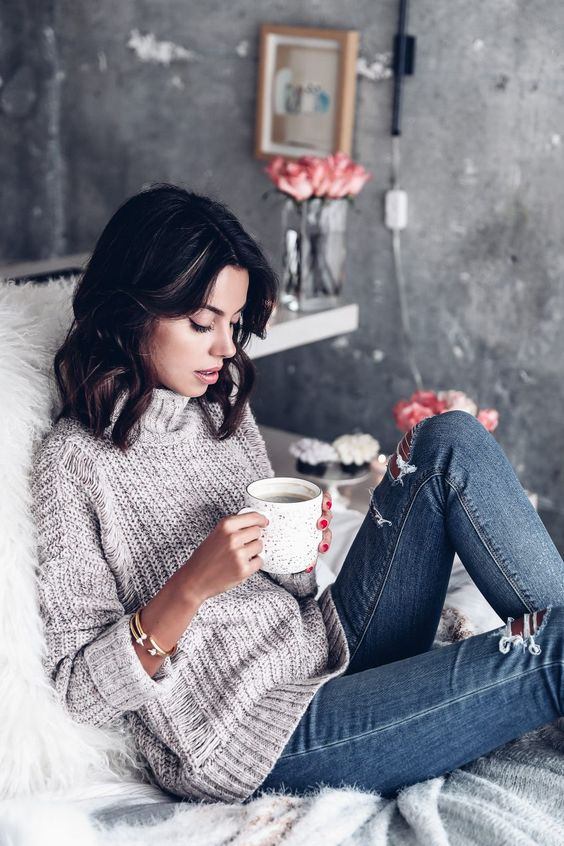 ripped jeans and a slouchy turtleneck sweater are ideal items to wear at home