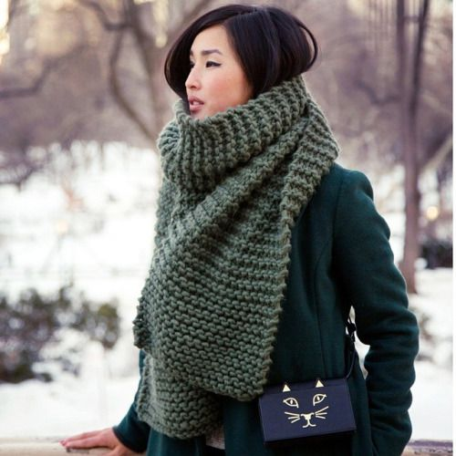an olive green chuky knit scarf over an emerald coat for a holiday feel