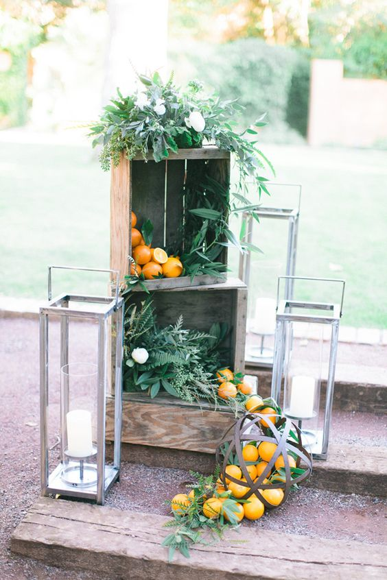 venue decor with crates filled with greenery and iranges, large candle lanterns around