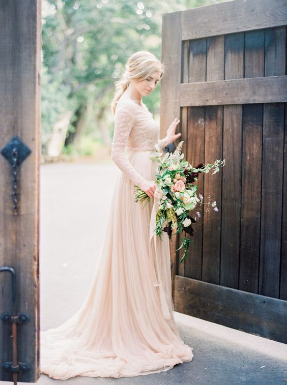 a cute blush wedding gown with a lace bodice and long sleeves and a sleek skirt