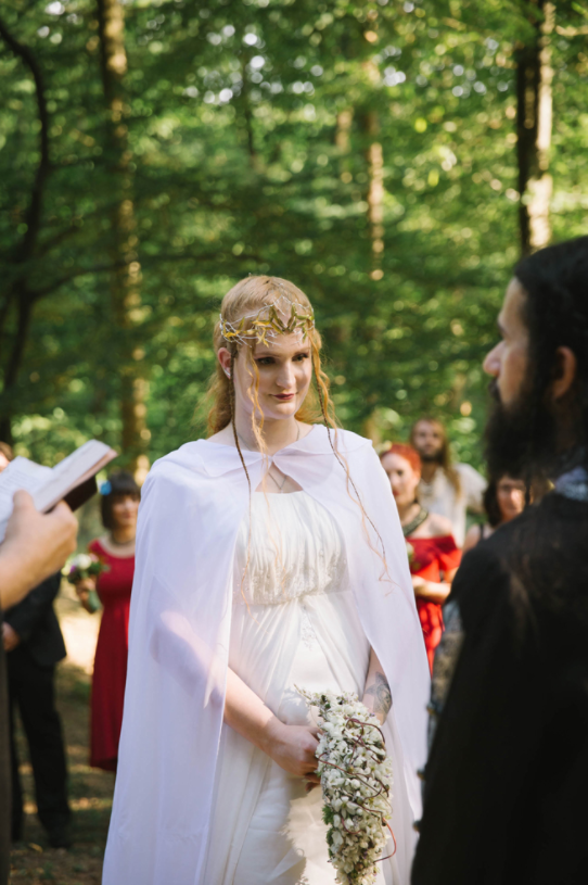 The bride was wearing a flowy light dress and a cap, a perfect elvish headpiece and a braided half updo