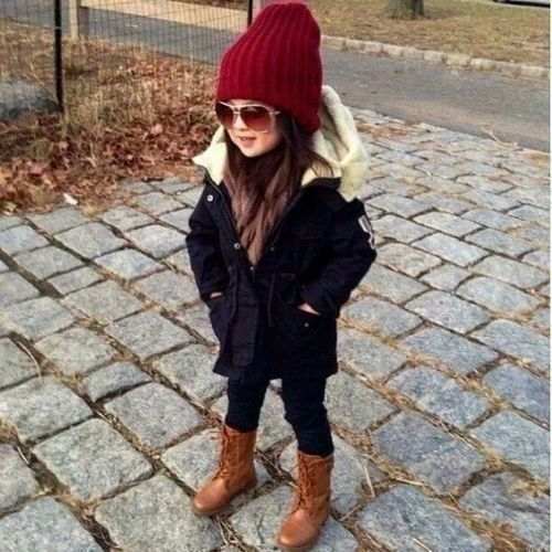 a black parka with white faux fur looks super chic with a red beanie