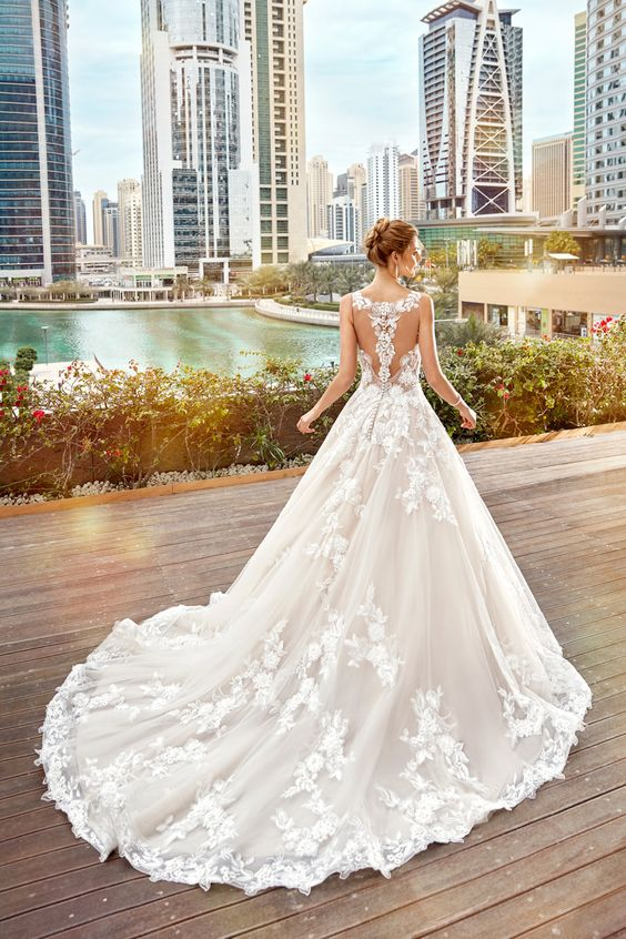 a gorgeous illusion back lace applique wedding dress with no sleeves and a train