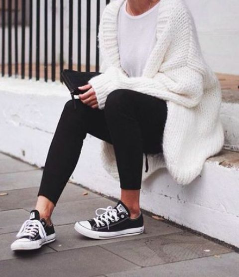 black leggings, a white tee, black sneakers and a white chunky cardigan