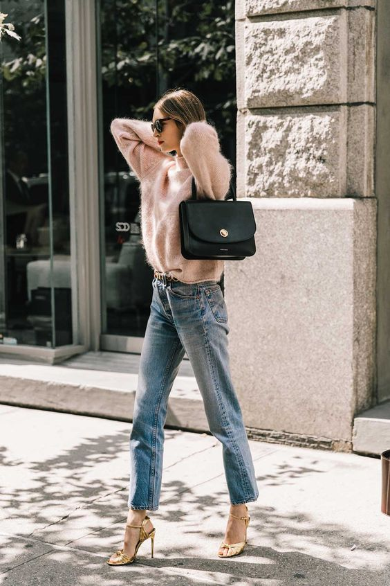 a pink angora sweater, hgh waisted blue jeans, gold shoes and a black bag
