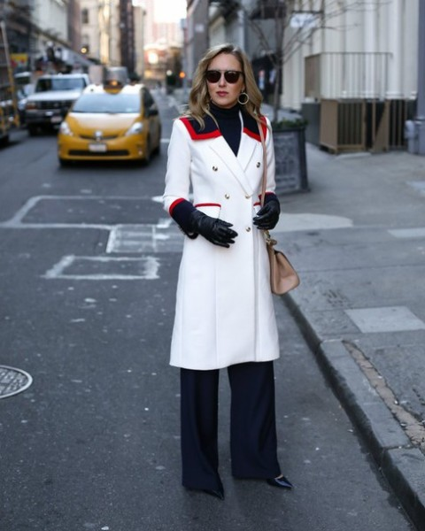 With navy blue trousers, black turtleneck, white coat and beige bag