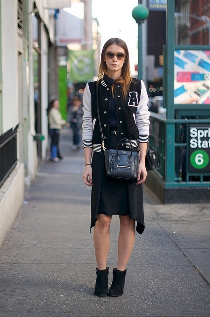 With navy blue shirt, knee-length skirt, ankle boots and bag